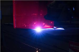 A plasma-burning machine cuts the first steel plate that will be used to build the ballistic