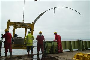 The bespoke drill rig being lowered over the side of the RRS James Cook.