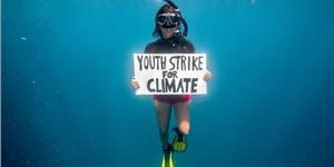 Climate activist Shaama Sandooyea holds a placard reading 'Youth Strike For Climate' in support of